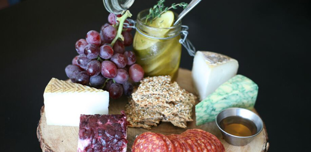 Image of cheeses, grapes and sliced salami on board